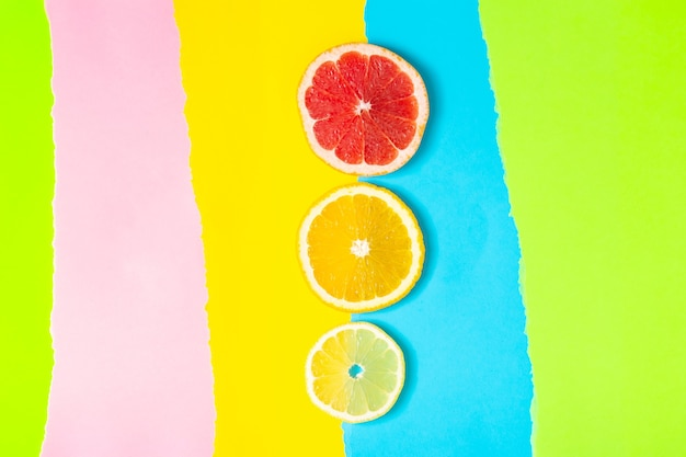 Красочная фруктовая тропическая композиция из свежих цитрусовых, лимона, апельсина и грейпфрута на ярком фоне. летняя еда творческая плоская планировка.