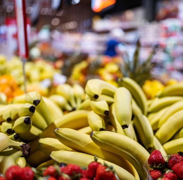 농산물 시장 근접 촬영에 있는 다채로운 과일과 열매, 식료품 바자에서 판매되는 바나나와 딸기