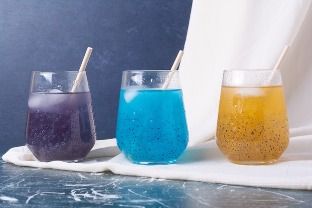 Colorful fruits in cups of drink on blue.