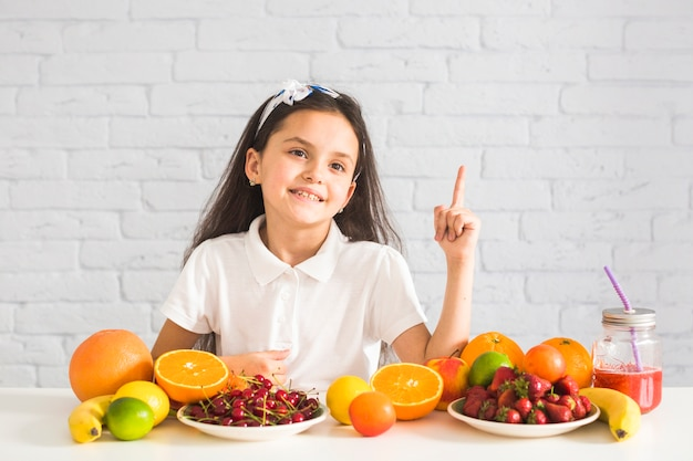 Colorful fruits in front of a girl pointing finger upward
