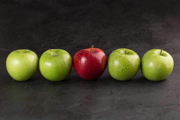 다채로운 과일 하나의 빨간색과 네 개의 녹색 부드러운 신선한 잘 익은 사과 회색 책상에 고립