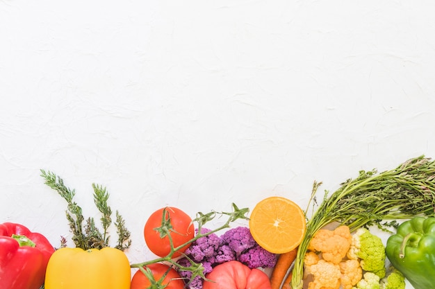 Colorful fruits and vegetables on white textured background