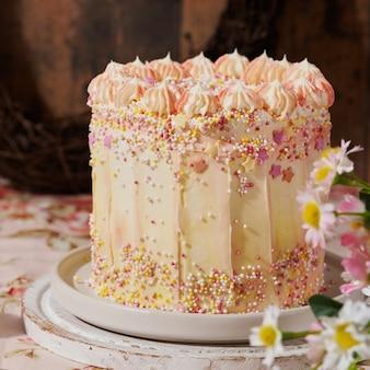 木製のカラフルな振りかけるで飾られたカラフルな楽しい黄色のケーキ