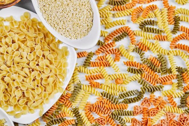 Красочные фузилли и другие сырые макаронные изделия на белом.