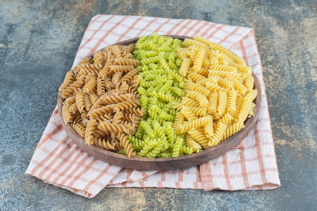 Colorful fusilli pastas in bowl on towel, on the marble background.