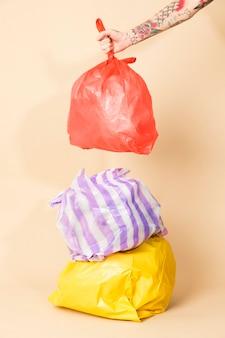 노란색 배경에 고립 된 다채로운 쓰레기 봉투