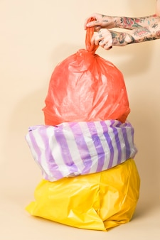 Colorful garbage bags on yellow background