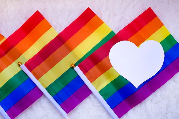 Colorful gay pride flags with a white heart on the left.