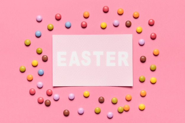 Colorful gem candies surrounded around the paper with easter word on pink backdrop