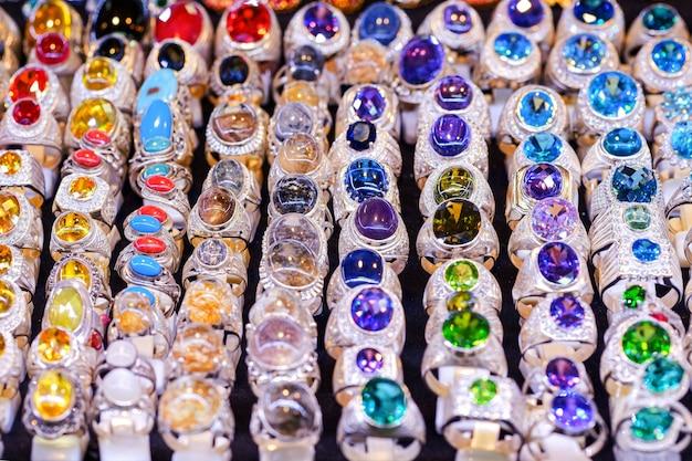 カラフルな宝石が市場のテーブルに鳴り響き、美しさのために指を着用するために使用されます。