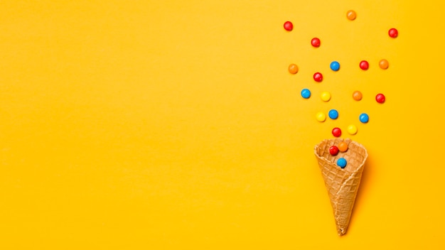 Colorful gems spilled from waffle cone on yellow backdrop