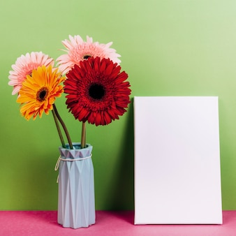Colorful gerbera flower vase near the blank card against green background