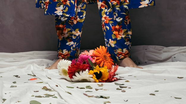 Colorful gerbera flowers in front of man's foot
