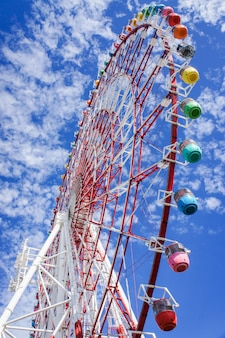 Colorful giant ferris wheel with blue sky and cloud