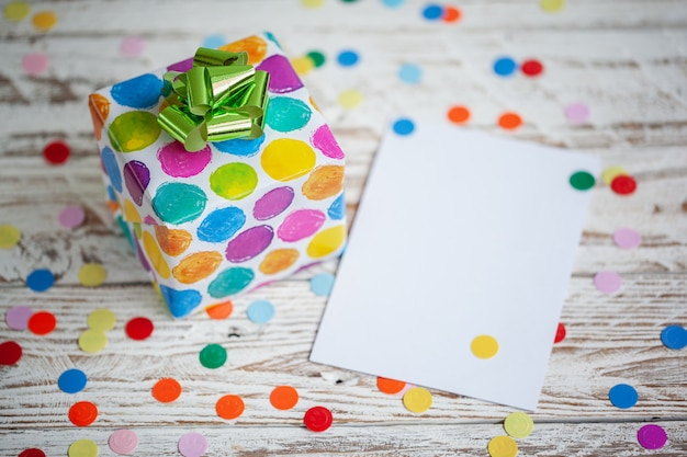 Colorful gift box with empty blank on wooden table. holiday greeting card.