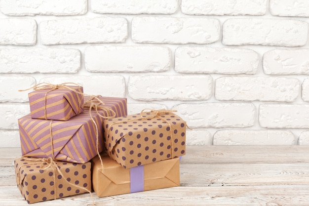 Colorful gift boxes against white brick wall