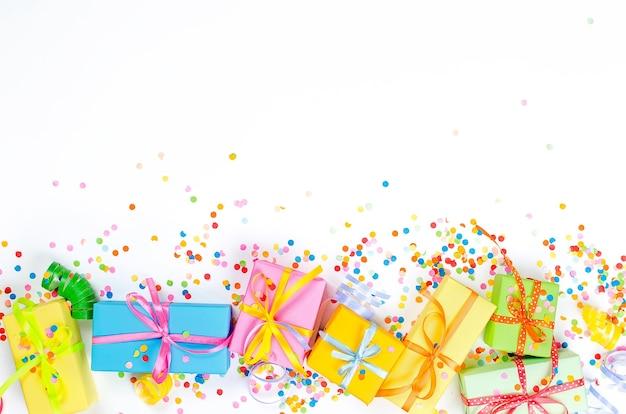 Красочные подарочные коробки, бумажные конфетти и закрученный серпантин для вечеринок на белом фоне