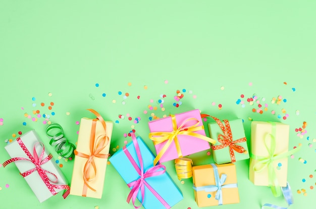 Colorful gift boxes, paper confetti and twirled party serpentine on a green background