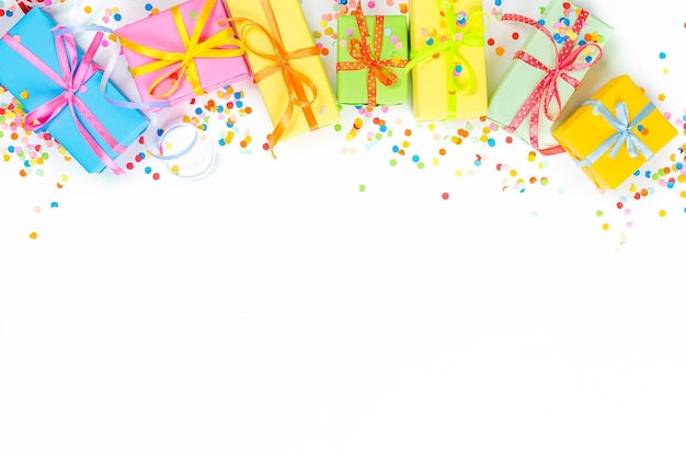 Colorful gift boxes, paper confetti and twirled party serpentine on a white background