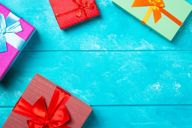 Colorful gift boxes with ribbons on nice blue wooden background