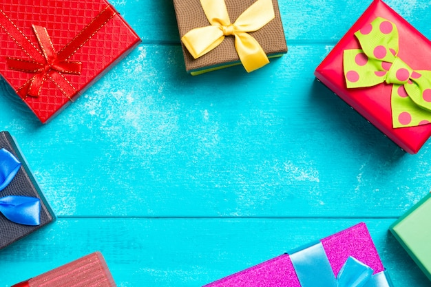 Colorful gift boxes with ribbons on nice blue wooden background.