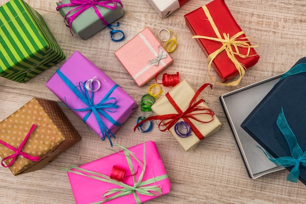 Colorful gift boxes on wooden table top view. presents, new year and christmas celebration