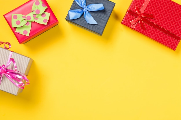 Colorful gift boxes on yellow  background