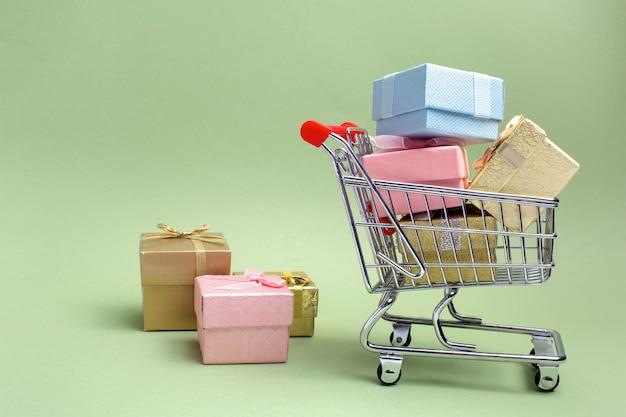 다채로운 선물 상자, 녹색 배경에 슈퍼마켓 쇼핑 카트