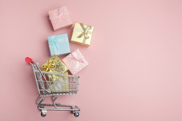 Красочная коробка подарков, тележка супермаркета на розовом фоне