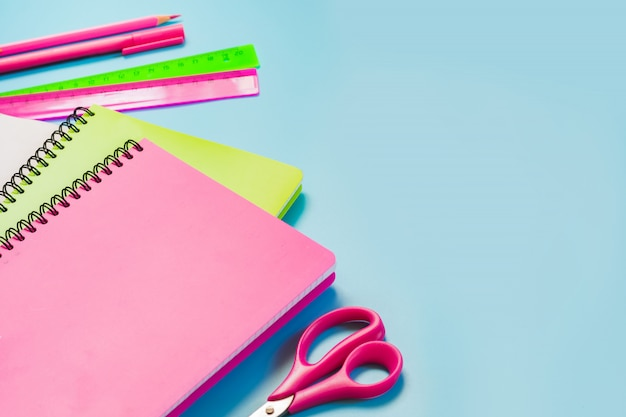 Colorful girlish school supplies, notebooks and pens on punchy blue. top view, flat lay. copy space.