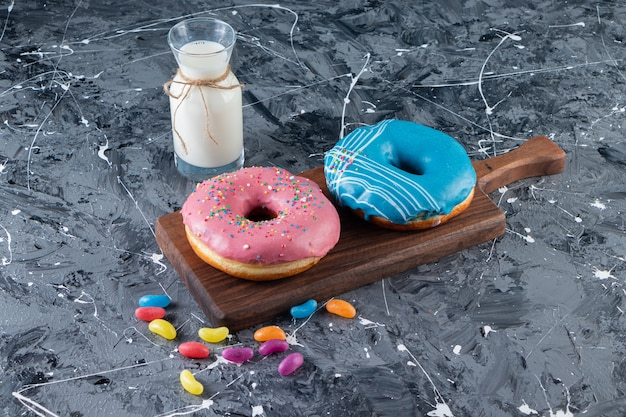 Colorful glazed doughnuts on a marble table.
