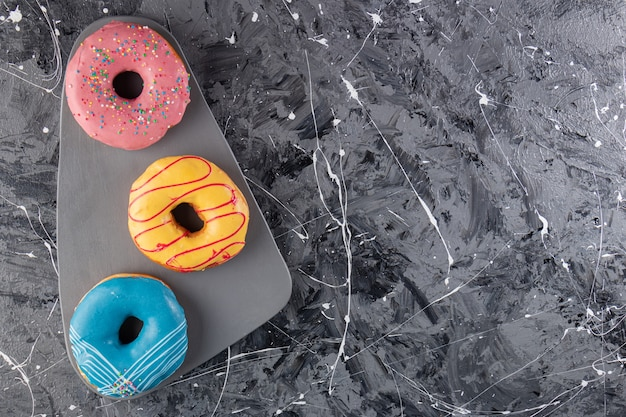 Colorful glazed doughnuts placed on marble table.