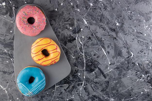 大理石のテーブルに置かれたカラフルな艶をかけられたドーナツ。