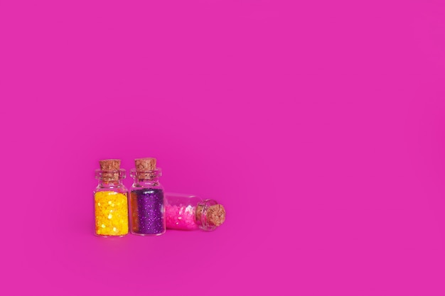 Colorful glitter in bottles with copyspace