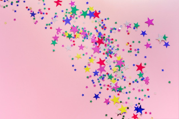 Colorful glitter stars decoration, merry christmas, happy new year isolated on pink background. stars shaped confetti