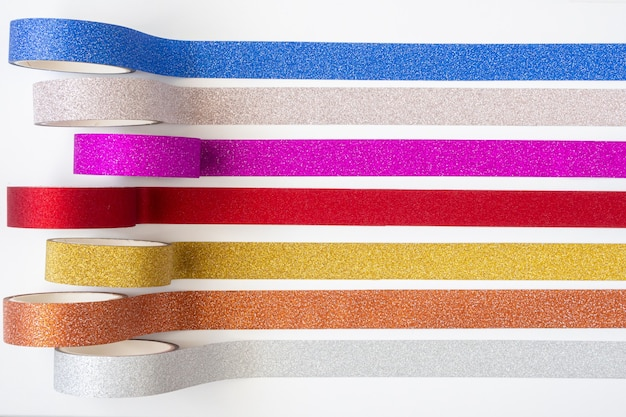 Colorful glitter tape rolls strips on white background
