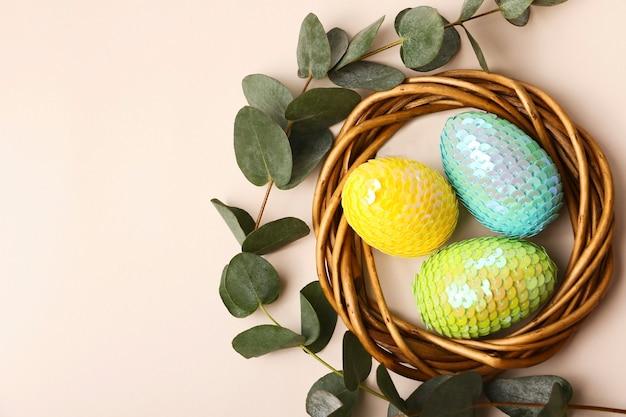 등나무 둥지에 다채로운 광택 부활절 달걀입니다. 뒷면에 천연 유칼립투스 분기입니다. 텍스트 또는 디자인을 위한 공간을 복사합니다.
