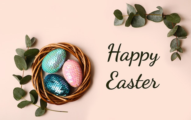 Colorful glossy easter eggs in the rattan nest.natural eucalyptus branch on the back.happy easter text.