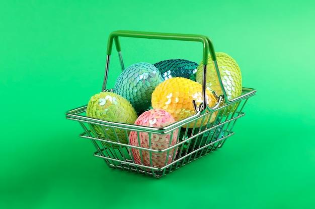 スパンコールとカラフルな光沢のあるイースターエッグ。鮮やかな色。買い物かごに横たわっている卵のグループ。