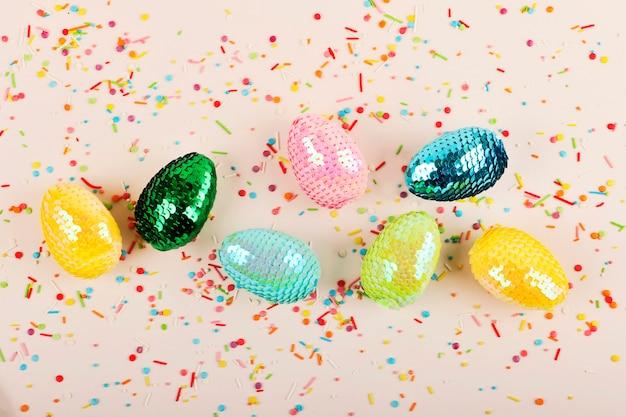 장식 조각으로 다채로운 광택 부활절 달걀입니다. 파스텔 배경에 생생한 과자 토 핑입니다. 축제 배경입니다.