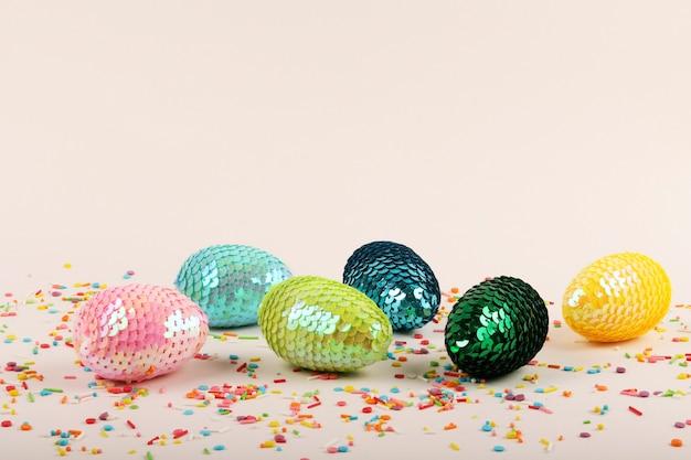 장식 조각이 있는 다채로운 광택 부활절 달걀입니다. 파스텔 배경에 생생한 패스트리 토핑이 있습니다.