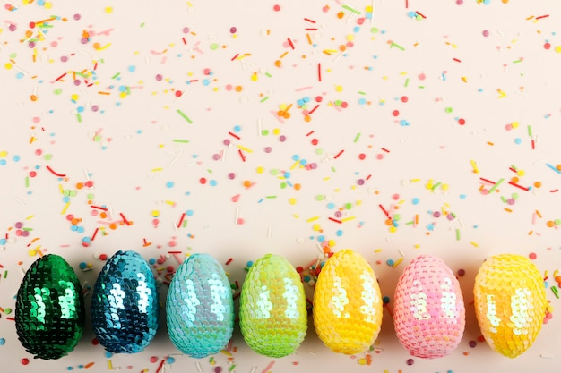 Colorful glossy easter eggs with sequins.vivid pastry topping on the pastel background.festive background.interesting flat lay.creative row of multicolored eggs.