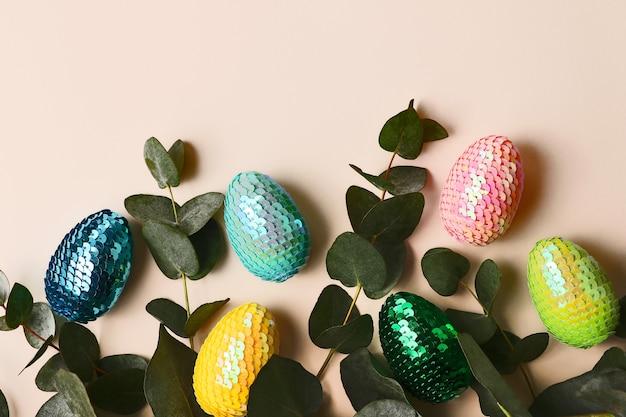 천연 유칼립투스 잎이 있는 다채로운 광택 있는 부활절 달걀.