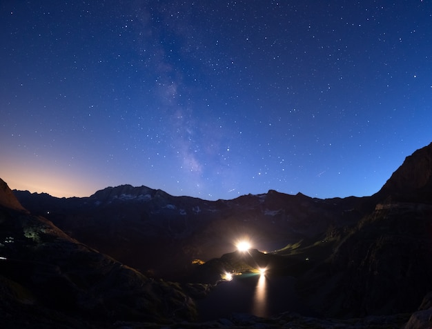 The colorful glowing milky way arch and the starry sky from high up on the alps. lights from hydroelectric lake dam.