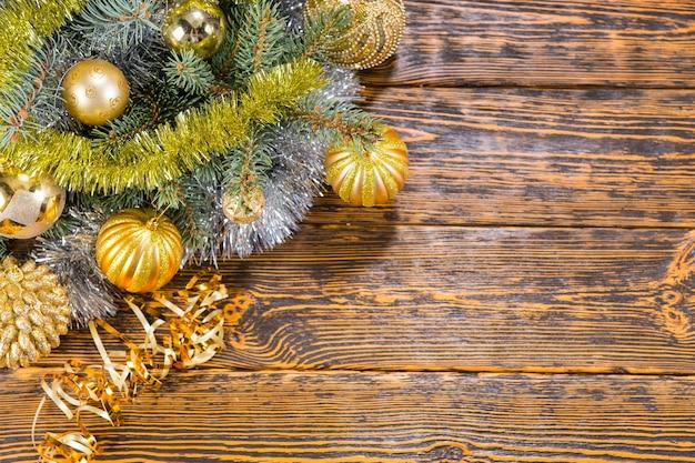 季節のメッセージのためのコピースペースと素朴な木製の背景の左上隅の松の葉に配置されたカラフルなゴールドのクリスマスつまらないもの