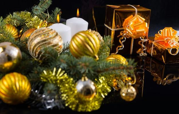 カラフルな金をテーマにしたクリスマスの静物画と松の枝に寄り添うつまらないものと、弓の付いた金箔の2つのエレガントなギフト、コピースペースのある暗い背景