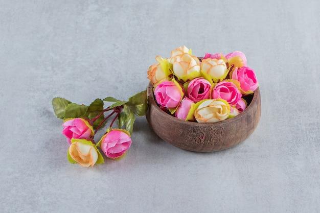 白いテーブルの上に、ボウルにカラフルな優雅な花。