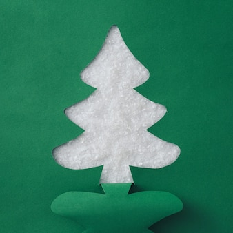 Colorful green christmas tree paper cutout over sparkling white snow with copyspace for your holiday message or greeting in a creative handmade card