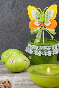 Colorful green easter eggs and lit candle