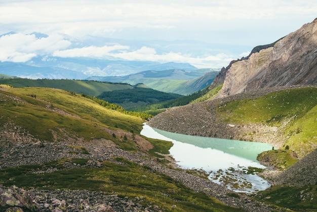 햇빛에 아름 다운 청록색 산 호수와 다채로운 녹색 풍경. 숲과 낮은 구름이 있는 푸른 산의 배경에 청록색 호수가 있는 인상적인 풍경. 경치 좋은 산 전망.